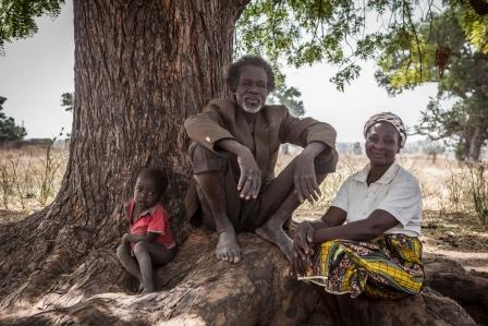 Grace Ulo a sorghum  farmer with her husband and grandson Junior, bith who she helps support with her farming.